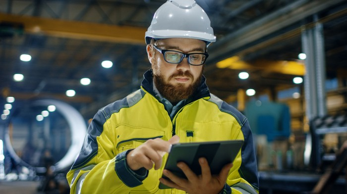 Man in hard hat looking at tablet