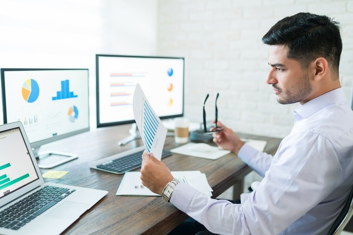 A businessman looking at several charts on monitors and paper.