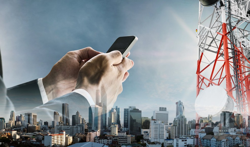 Businessman using smartphone over cityscape and wireless antennas