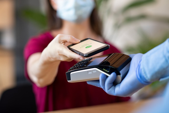 Merchant holding mobile phone over payment terminal
