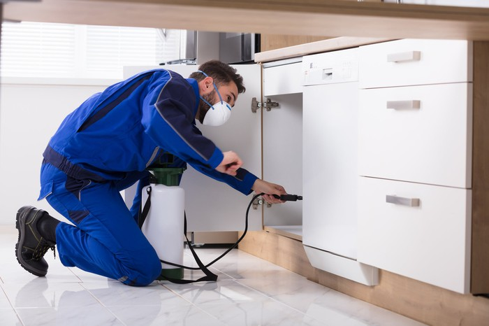 Pest control technician spraying in cabinets