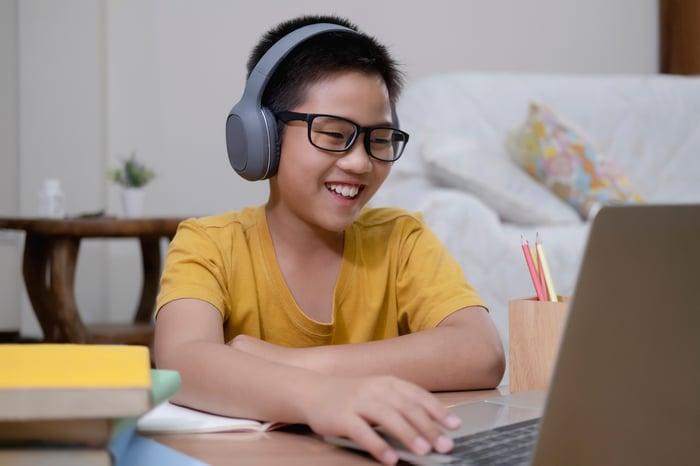 A young boy studies on a laptop.