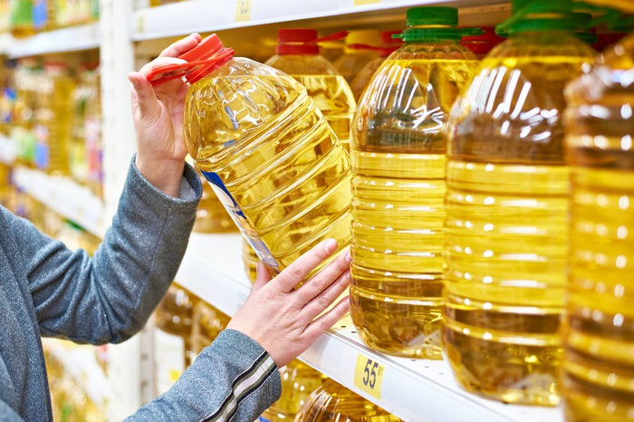 Customer grabbing a bulk-size container of cooking oil.