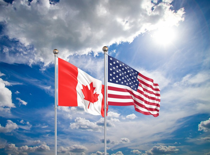 US and Canadian flags fly side by side against a cloudy blue sky.