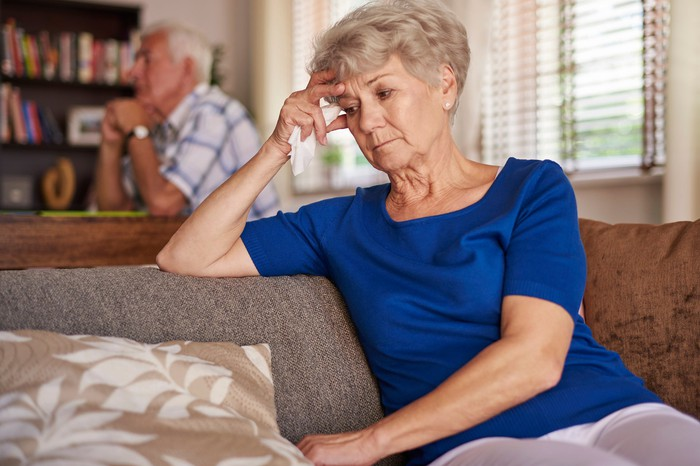 Worried senior woman on couch with her head in her hands with concerned husband behind her
