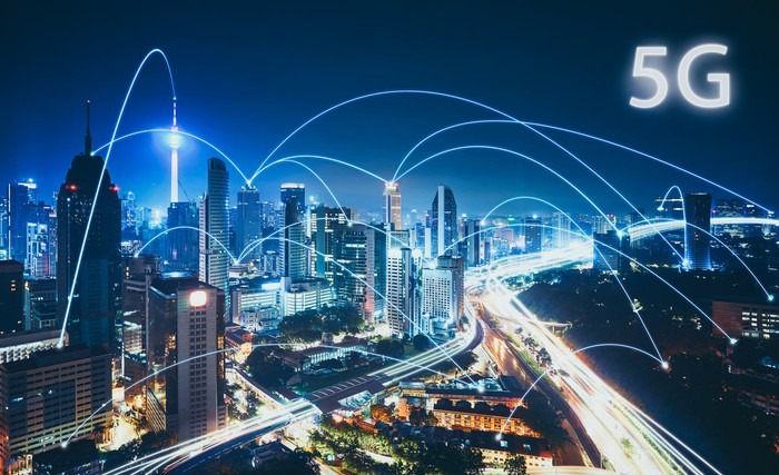 A city skyline at night with an interconnected web of 5G links hovering above it