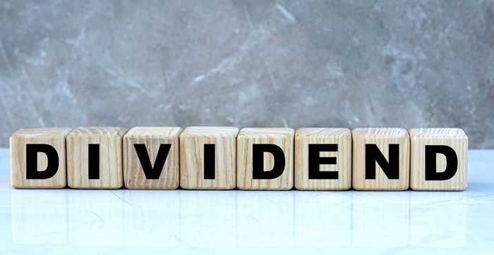 """The word """"dividend"""" written out in wooden blocks."""