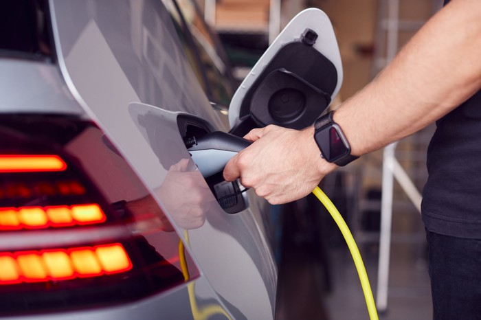 A Man attaches a power cable to an electric vehicle.
