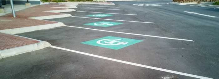 A row of clearly marked but empty car-charging parking spots.