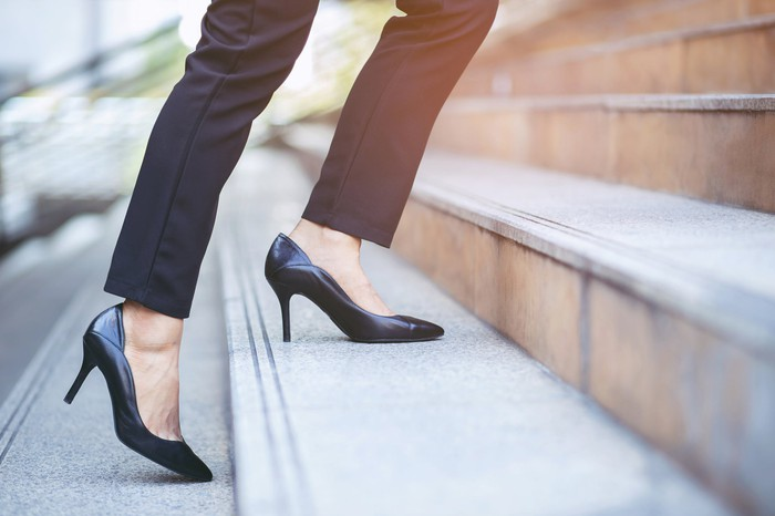 Person wearing high heels walking up the outdoor steps of a building