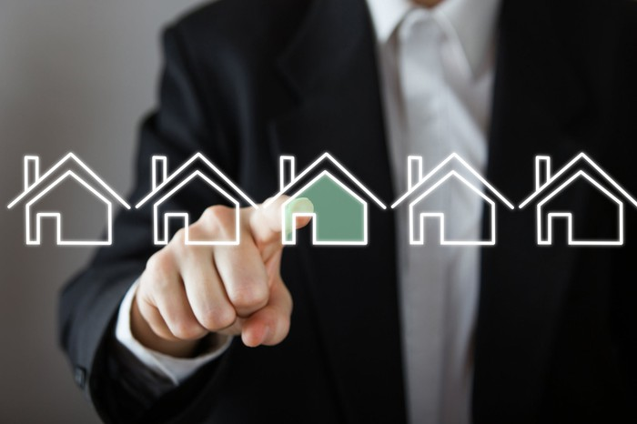 A person is pointing to a digital image of a home.