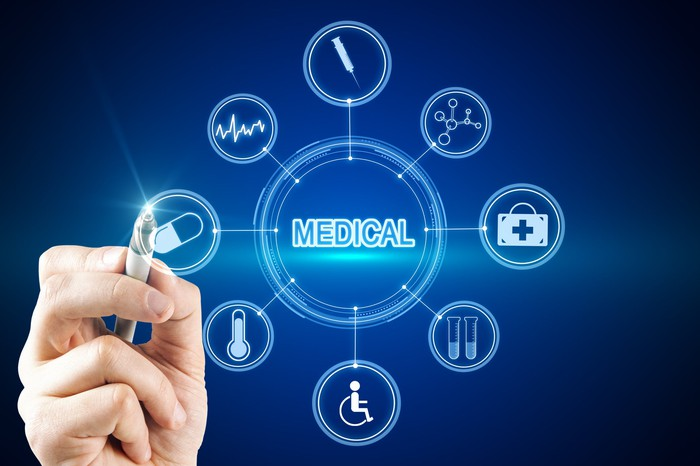 Hand with pointer pointing to a screen showing various healthcare-related icons.