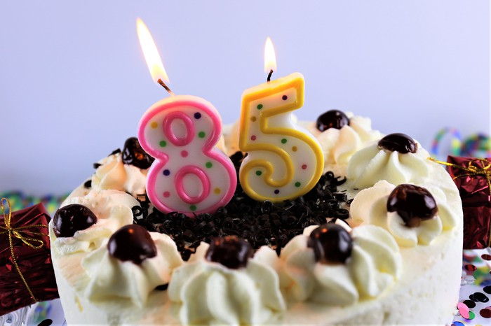 A birthday cake with lit number candles that read eighty-five.