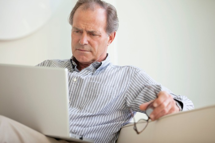 A mature man holding his glasses while reading material on his open laptop.