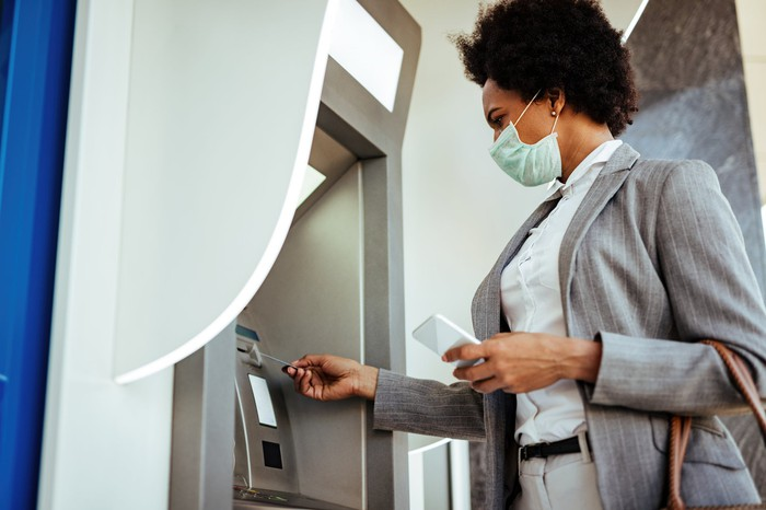 A woman in a mask uses an ATM.