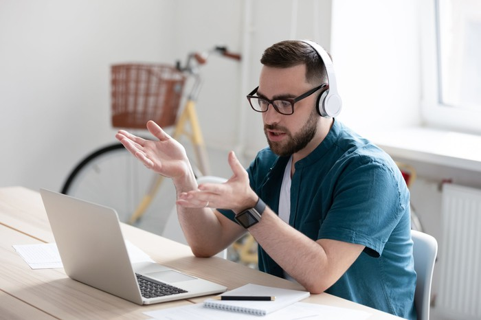 A man sits at a table with a laptop in front of him, wearing headphones and gesturing at the screen