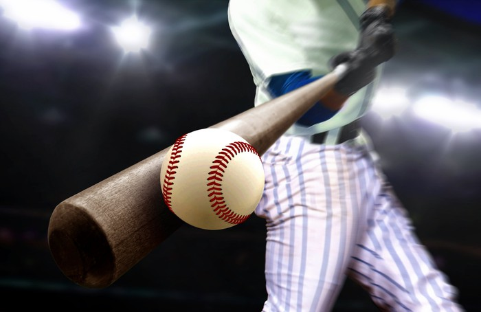 A baseball player hitting a ball.