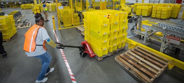 Amazon.com employee pulling crates at warehouse