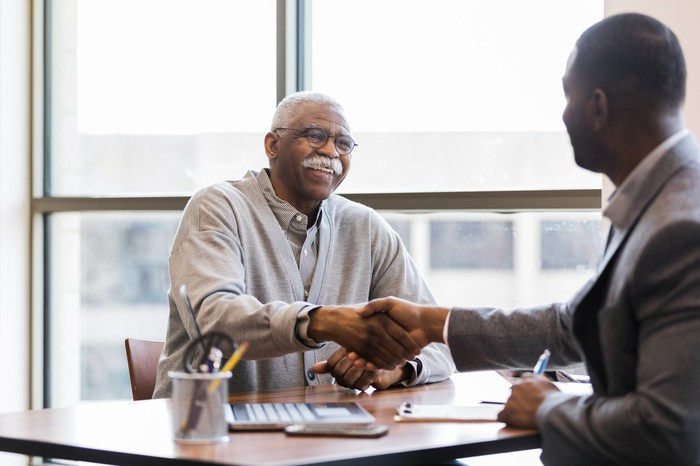 A senior man shakes hands with a retirement professional.