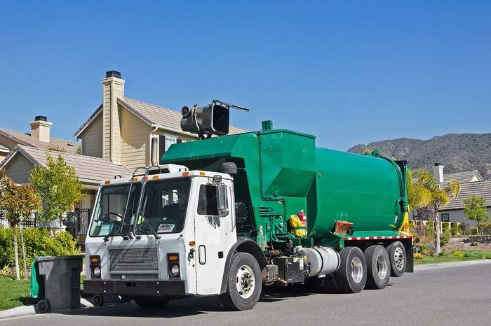 A garbage truck picking up a garbage can in front of a house
