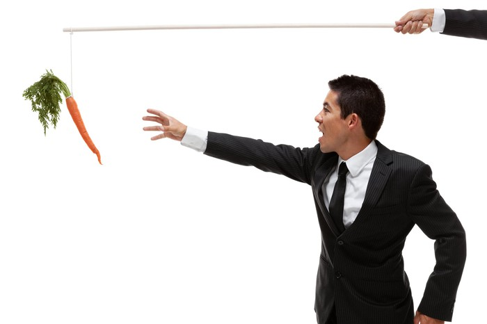 A businessman reaches for a carrot dangling from a string.
