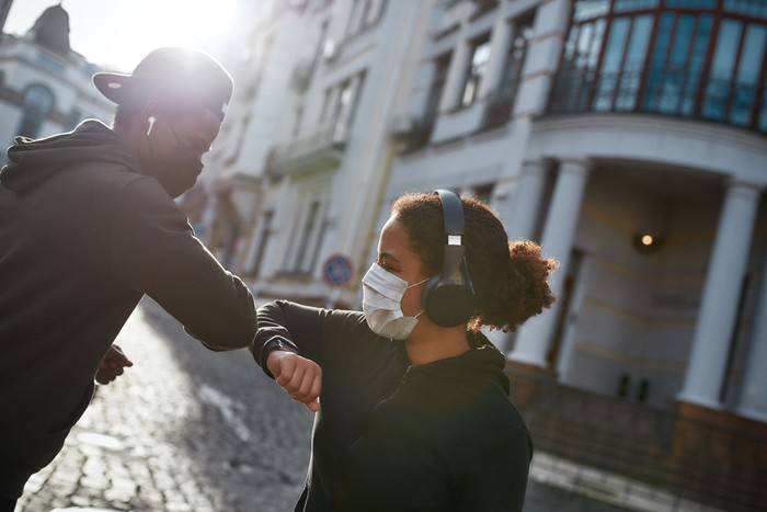 A young exercising couple wearing masks bump elbows to greet each other.