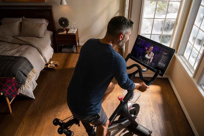 A man exercises with a Peloton Bike in a bedroom with wood floors.