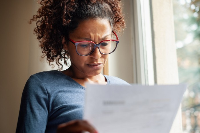 A women consults a bill with a pained expression.