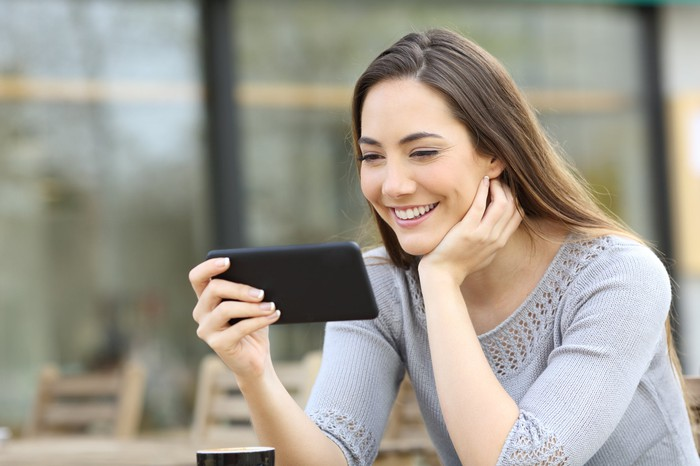 Woman smiling while looking at smartphone.