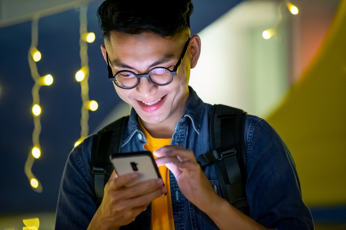 Smiling young man with face lit up by smartphone.
