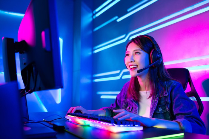 Young woman in a dark room wearing headset at a gaming computer with a multicolor keyboard