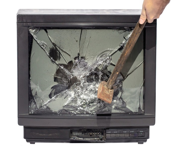 A hand smashes a television set with a hammer.