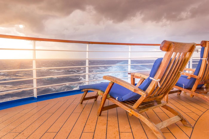 Two deck chairs on a wooden deck on a ship, overlooking sunset and ship wake.