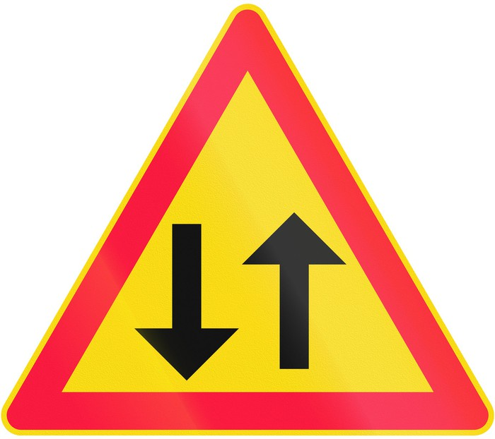 Caution sign with an up and a down arrow inside a red border on a yellow background