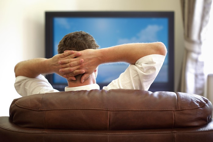Viewed from behind a man lounges on his couch with arms behind head watching TV.