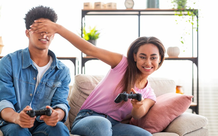 Teenage couple sitting on a couch, clowning around, playing video games.