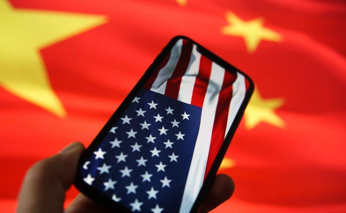 An iPhone displaying an American flag with a Chinese flag in the background.
