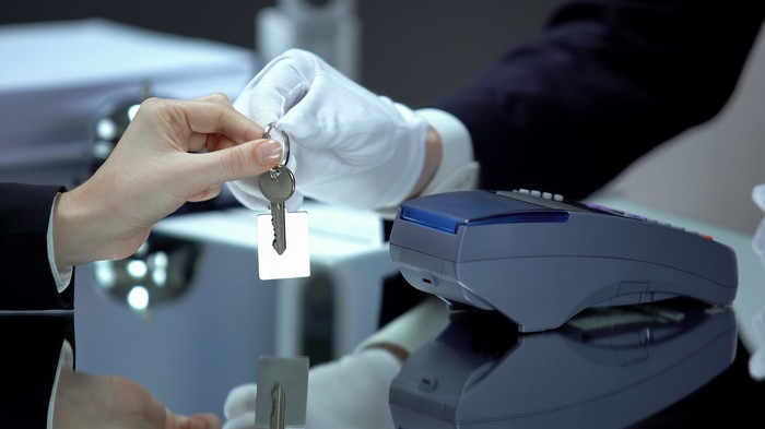 A gloved hotel receptionist hands over a key to a traveler after a contactless payment.