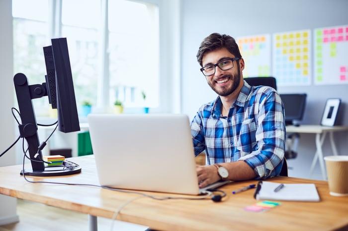 Smiling man at laptop.
