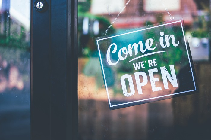 """A sign outside of a restaurant saying, """"Come in we're open."""""""
