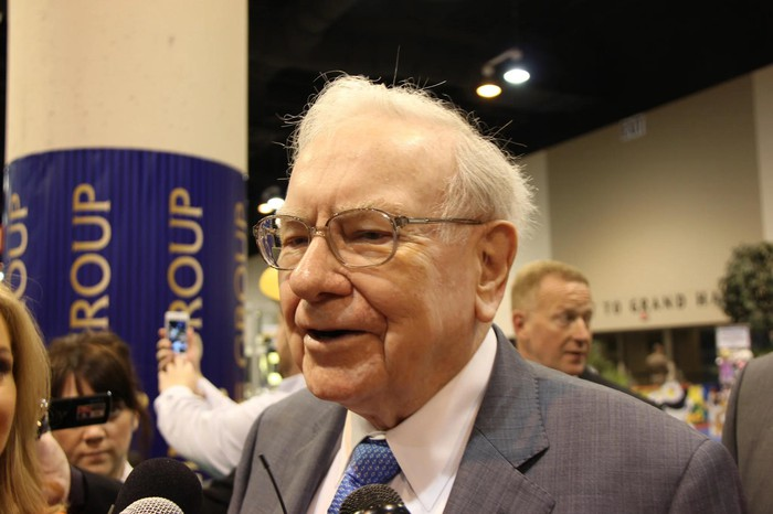 Warren Buffett in a convention center, with people surrounding him.
