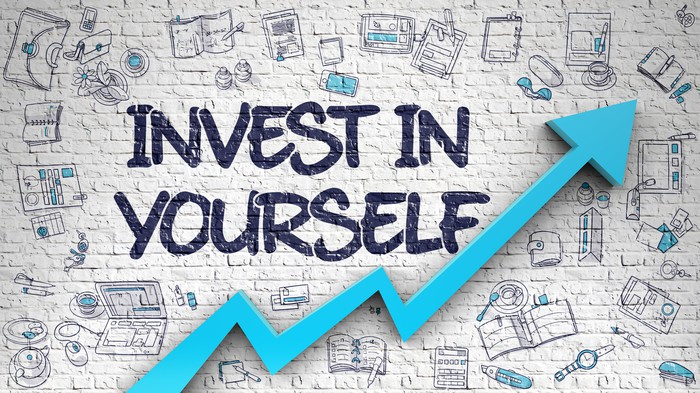 """""""Invest in Yourself"""" Written along a white brick wall."""