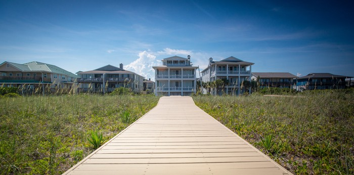 A long, wooden boardwalk leads to a vacation house rental at a beach.