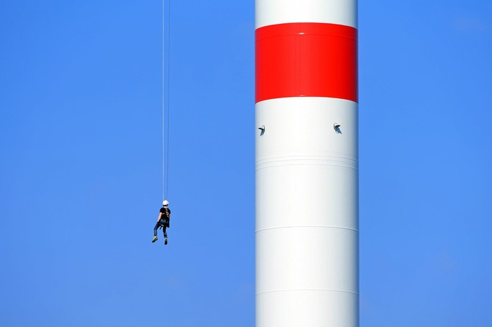 Worker suspended from a cable on a wind turbine.