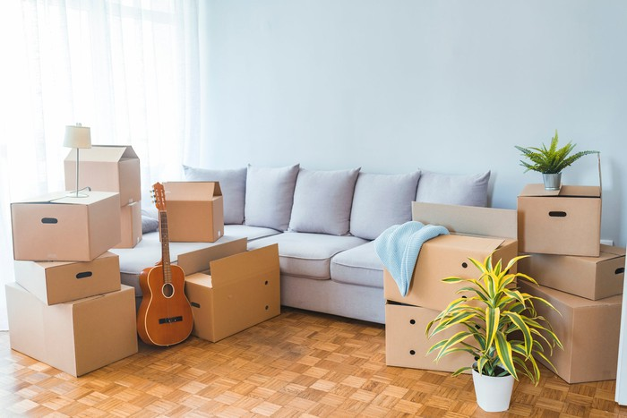 A brightly lit living room with moving boxes and a sofa.
