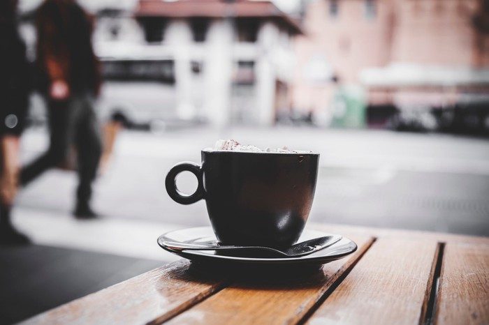 A cup of coffee sitting on a plate with a spoon on a wooden table outdoors.