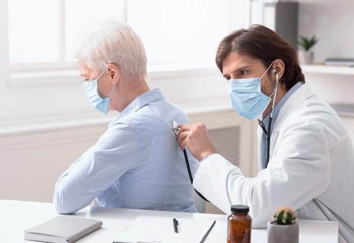 Masked doctor pressing stethoscope into masked older patient's back