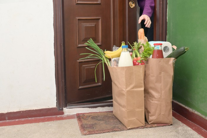 A person opens apartment door to retrieve bags of groceries delivered
