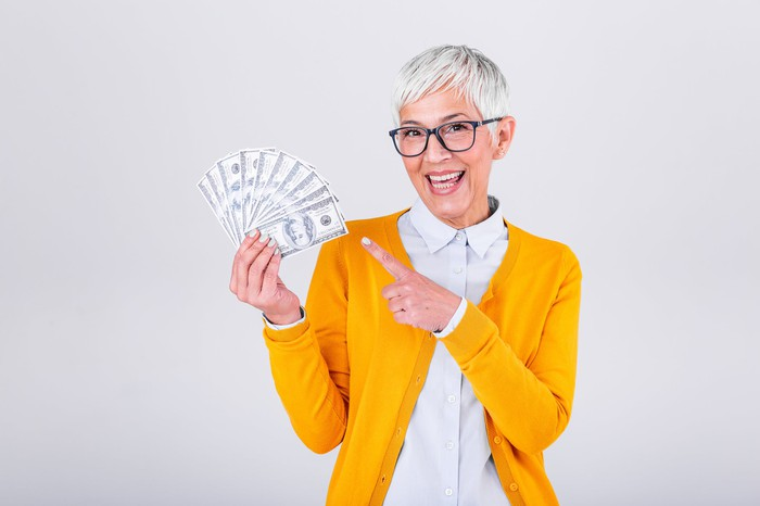 A happy senior woman is smiling and pointing to a handful of cash.