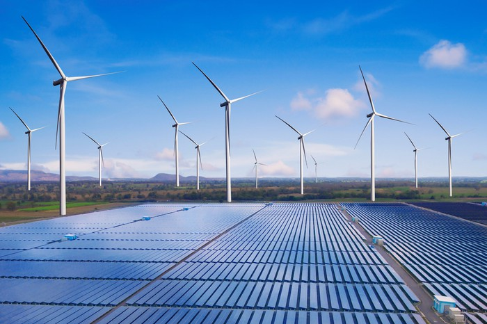 Wind turbines and solar panels in an open field.